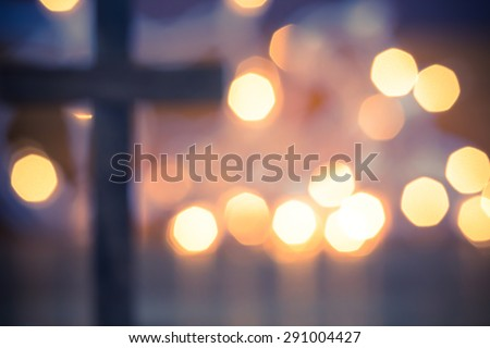 Wooden Christian Cross out of focus with a soft bokeh lights background - stock photo