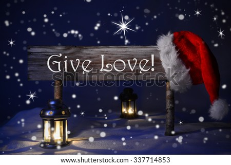 Wooden Christmas Sign And Santa Hat With Snow In Snowy Scenery. English Text Give Love For Seasons Greetings. Blue Silent Night With Snowflakes And Sparkling Stars. Lantern And Candlelight - stock photo