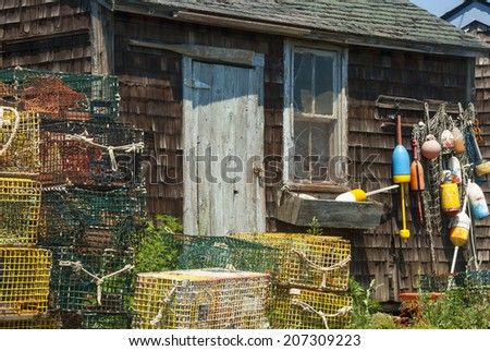 Wooden Clapboard Building Surrounded by Lobster Traps, Lobster Buoys and Floats - stock photo