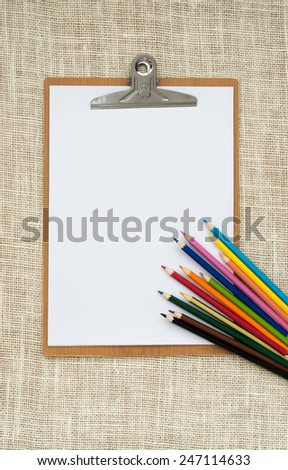 wooden clipboard and colored pencils on old sackcloth background, with regular white blank paper. - stock photo
