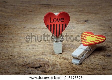 wooden clips with love letters and heart shape on wooden table - stock photo