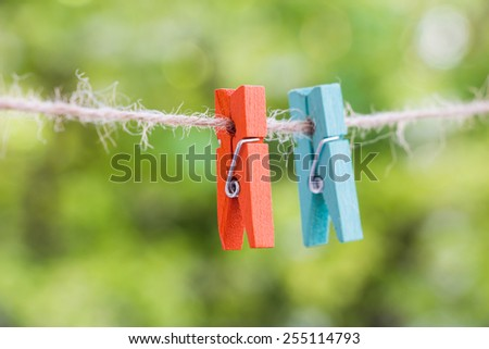 wooden clothespin hanging on rope, depth of field - stock photo