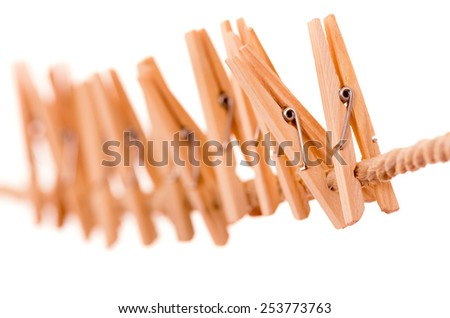 wooden clothespins hanging on rope isolated on white selective focus - stock photo
