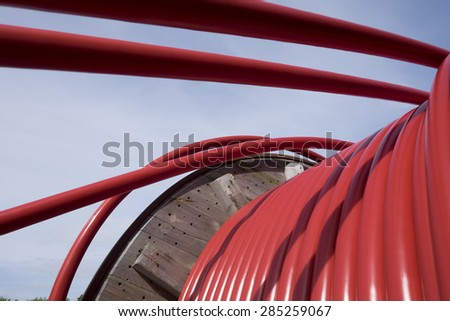 Wooden Coil of Red Electric Cable Outdoor - stock photo