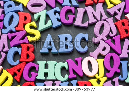 Wooden colorful ABC alphabet letters on blackboard - stock photo