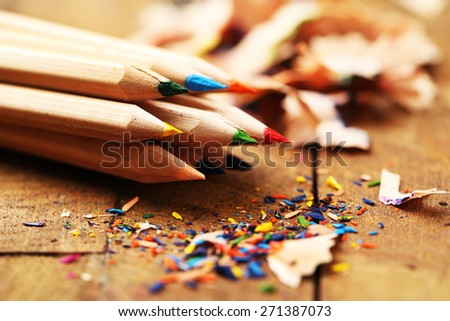 Wooden colorful pencils with sharpening shavings, on wooden table - stock photo
