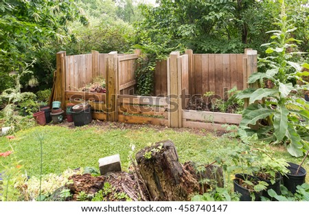 wooden compost bins in garden setting - stock photo
