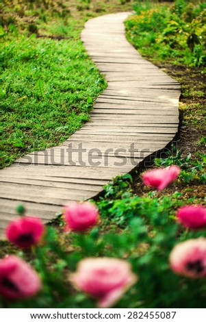 Wooden convoluted path in a spring garden in the morning - stock photo