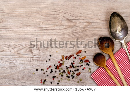 Wooden cooking spoon and old silver spoon on a checkered napkin - stock photo
