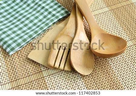 Wooden cooking utensils on wood background - stock photo