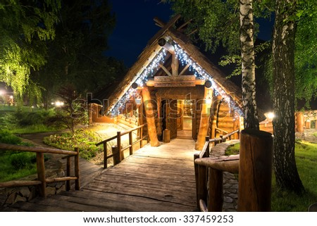 Wooden cottage in forest lit by lanterns at night - stock photo