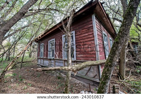 wooden cottage in small abandoned village called Stechanka in Chernobyl Nuclear Power Plant Zone of Alienation, Ukraine - stock photo