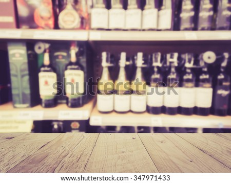 Wooden counter product display with Wine Liquor bottle on shelf, Blurred background - stock photo