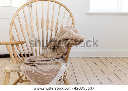 Wooden country style chair with textured throw blanket and negative space for text - stock photo