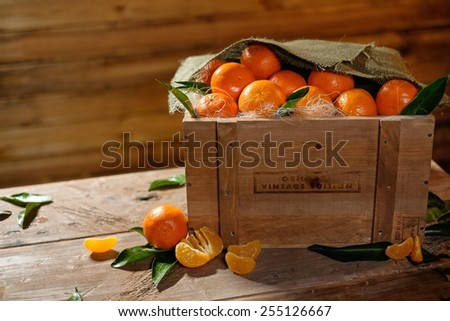 Wooden crate with tasty tangerines on a table  - stock photo