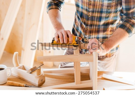 Wooden creation. Close-up of young male carpenter sanding wooden chair in his workshop  - stock photo