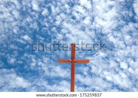 wooden cross against blue cloudy sky background - stock photo