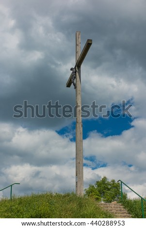 wooden cross against partly cloudy sky - stock photo
