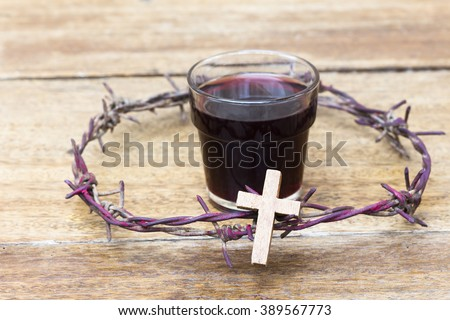 wooden cross and a cup of grape juice  with metal Barbed Wire made like the crown of thorns of Jesus on wooden background, Christian concept, Easter background with copy space - stock photo