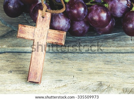 Wooden cross and grape on wooden background, christian symbol Jesus is the true vine from bible verses John 15:1 - stock photo