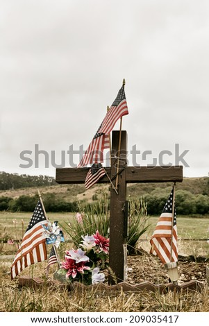 Wooden cross at a grave decorated with American flags. Faded vintage colors. Concepts: patriotism, soldier, fallen, memorial, veteran. Copy space. - stock photo