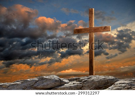 Wooden cross on rocky hill at sunset - stock photo