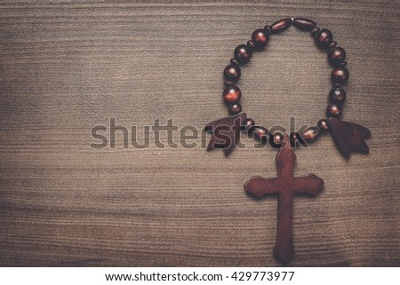 wooden cross on the brown table background - stock photo