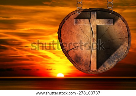 Wooden Cross on Tree Trunk at the Sunset / Wooden Christian cross on a section of tree trunk, hanging from a metal chain at the beautiful sunset over the sea with cloudy sky - stock photo