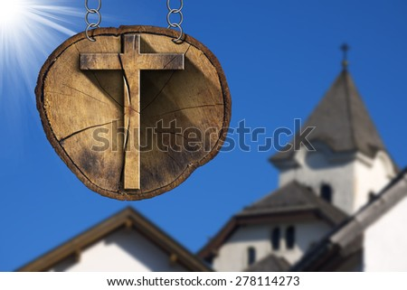 Wooden Cross on Tree Trunk with Church / Wooden Christian cross on a section of tree trunk, hanging from a metal chain. In the background the ancient roofs of a mountain sanctuary - stock photo