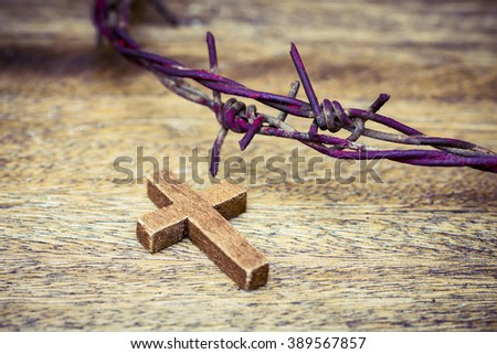 wooden cross  with  metal Barbed Wire made like the crown of thorns of Jesus on wooden background, Christian concept, Easter background with copy space - stock photo
