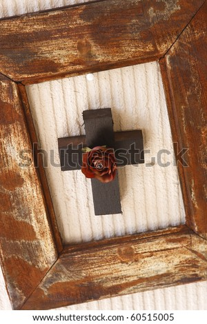 Wooden cross with rose inside a wooden frame - stock photo