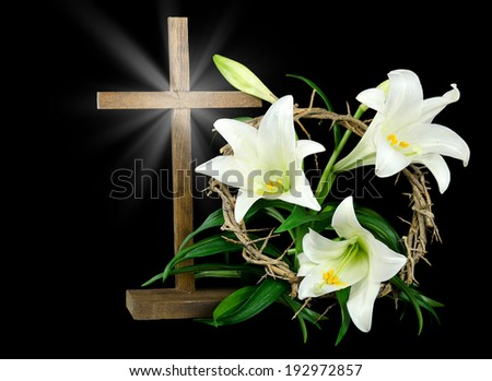 wooden cross with white Easter lilies and crown of thorns - stock photo