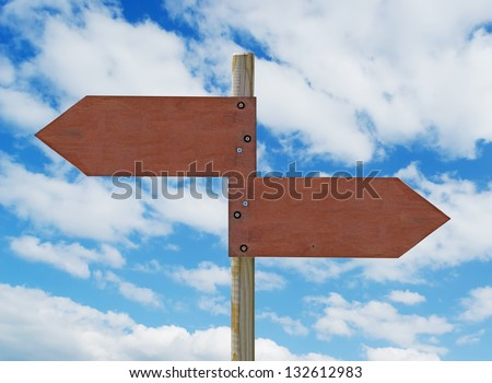 wooden crossroad sign on cloudy background - stock photo