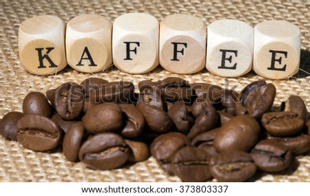 wooden cubes with the german word Coffee and Coffee beans lying on jute fabric / Coffee beans - stock photo