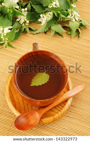 Wooden cup of nettle tea and spoon on bamboo mat - stock photo