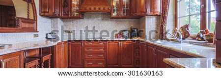 Wooden cupboards in kitchen in traditional style - stock photo