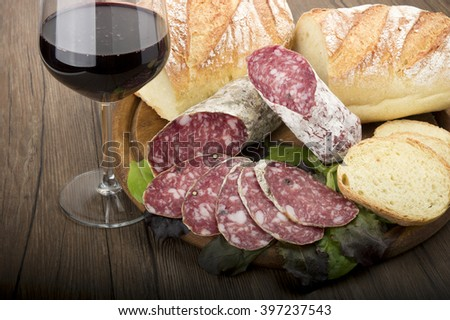 wooden cutting board with salami and glass of Red wine - stock photo