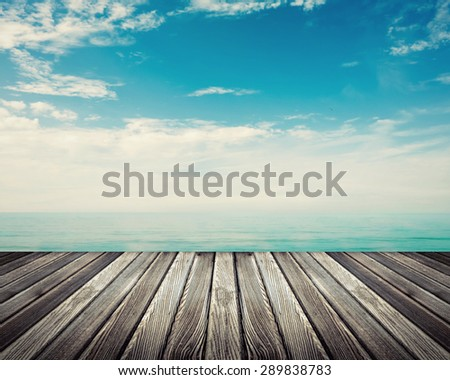 Wooden deck floor against ocean with cloudy sky in background - stock photo