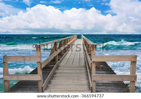 Wooden deck pier on the coast the azure sea against the blue sky. - stock photo