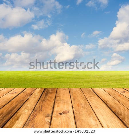 Wooden deck table over beautiful meadow with blue sky - stock photo