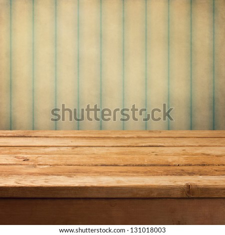 Wooden deck table over grunge vintage background - stock photo