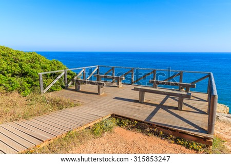 Wooden deck with benches for tourists on coast of Portugal in Carvoeiro town, Algarve region - stock photo