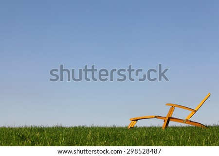 Wooden deckchair in a meadow with blue sky - stock photo