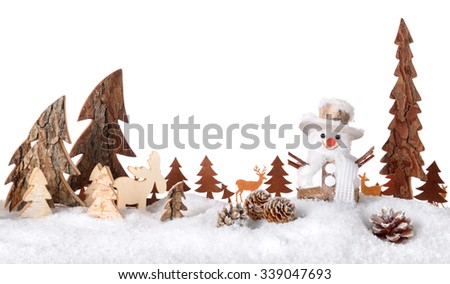 Wooden decoration arranged as a cute winter scene with a snowman, conifer trees, animals and snow, isolated on white background - stock photo