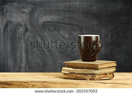 wooden desk books and mug  - stock photo