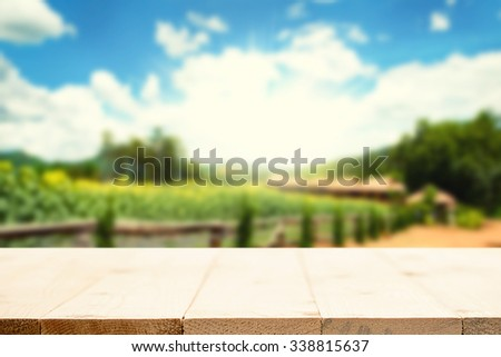 wooden desk space platform and farm of field background vintage tone. - stock photo