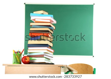 Wooden desk with books and chair in class on blackboard background - stock photo
