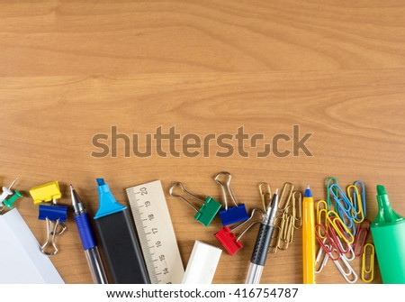 Wooden desk with lots of stationery objects below - stock photo