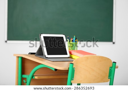 Wooden desk with stationery and tablet in class on blackboard background - stock photo