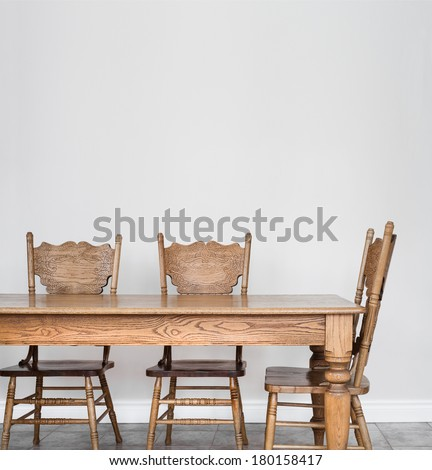 Wooden Dining room table and chair details and blank wall for your text, image or logo. - stock photo